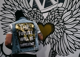 Artist painting a wall with 'The future will be different' written on the back of their jacket