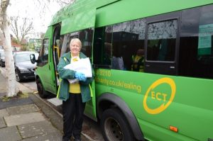 Photo of woman by the side of a green community transport bus holding a good parcel