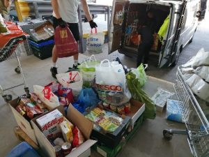 Boxes and bags of food donations being unloaded from a van