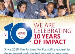 Photo of two adults with a group of schoolchildren with banner saying 'We are celebrating 10 years of impact'