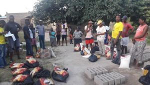 A group of people congregated into an open space with food parcels