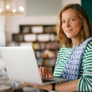 Photo of a woman with a teatowel draped over her shoulder holding a laptop