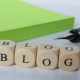 Wooden tiles spelling 'blog' with a pen and pad in the background