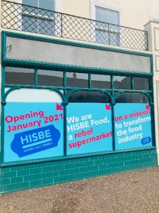 Photo of an empty store front with posters announcing a new HIBSE store opening in January 2021