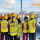 Photo of schoolchildren wearing hard hats and high vis jackets looking out of a window across a cityscape