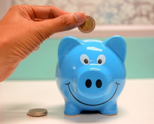 A hand putting a coin into a blue piggy bank
