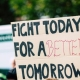 Photo of a crowd with someone holding a banner saying 'Fight today for a better tomorrow'