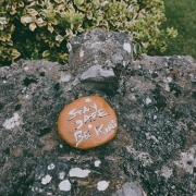 A pebble with text 'Stay safe and be kind' sat on a rock