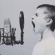 A boy shouting into a microphone