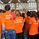 Group of people wearing orange t-shirts with 'Student Volunteer' on the back