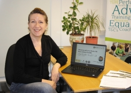 Photo of a woman sat at a desk in front of a laptop showing free recruitment toolkit