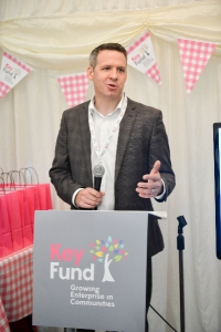 Matt Smith speaking behind a lectern branded with the Key Fund logo