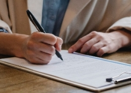 A person holding a pen over paper on a clipboard